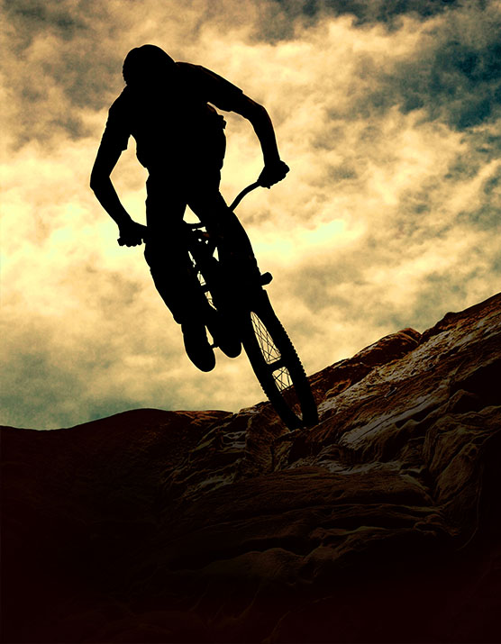 Man op muontain-bike, zonsondergang