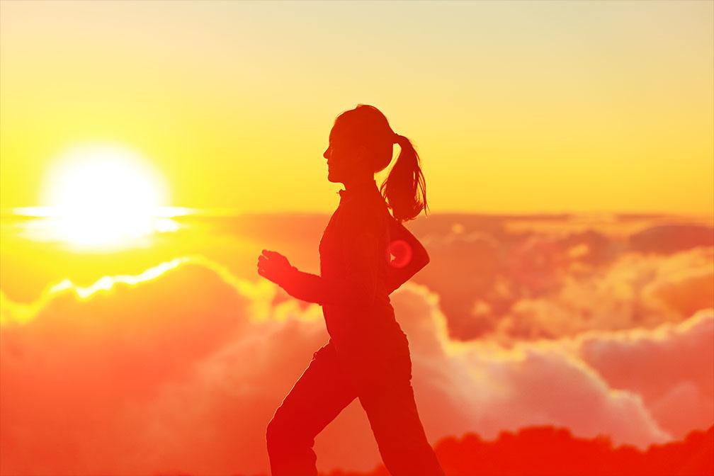 Runner vrouw bij zonsondergang