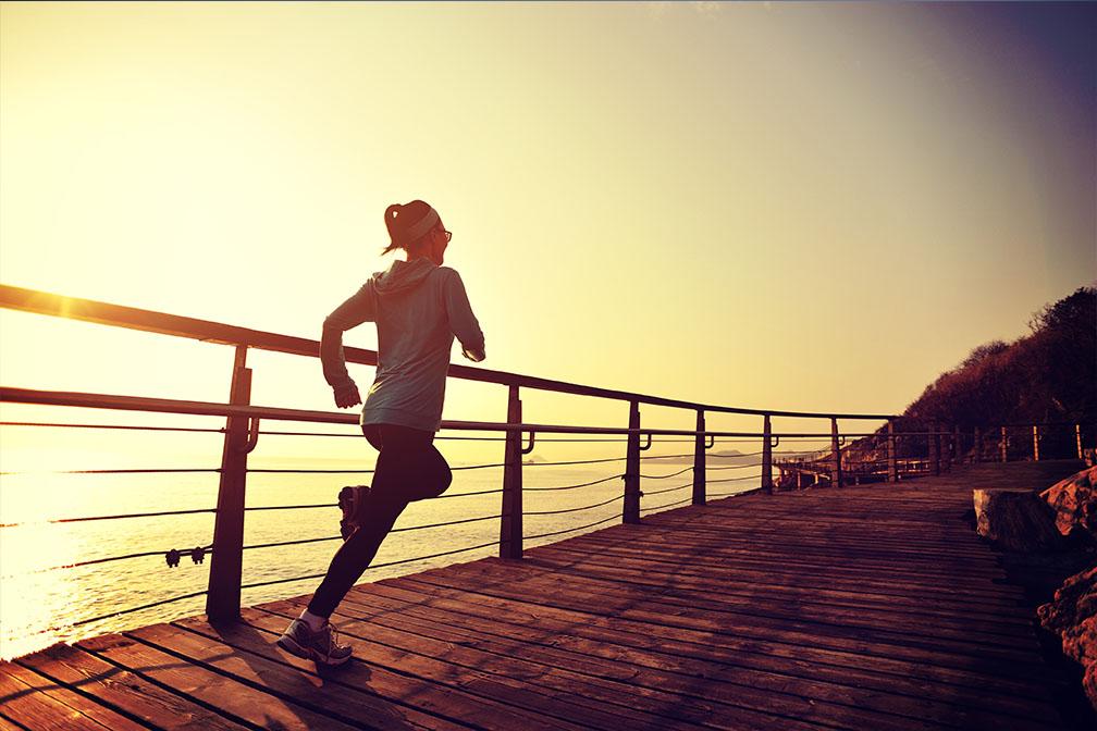 Vrouw rennend over houten vlonder