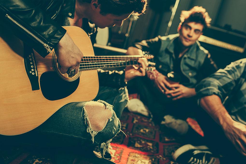 Muzikant speelt gitaar met vrienden