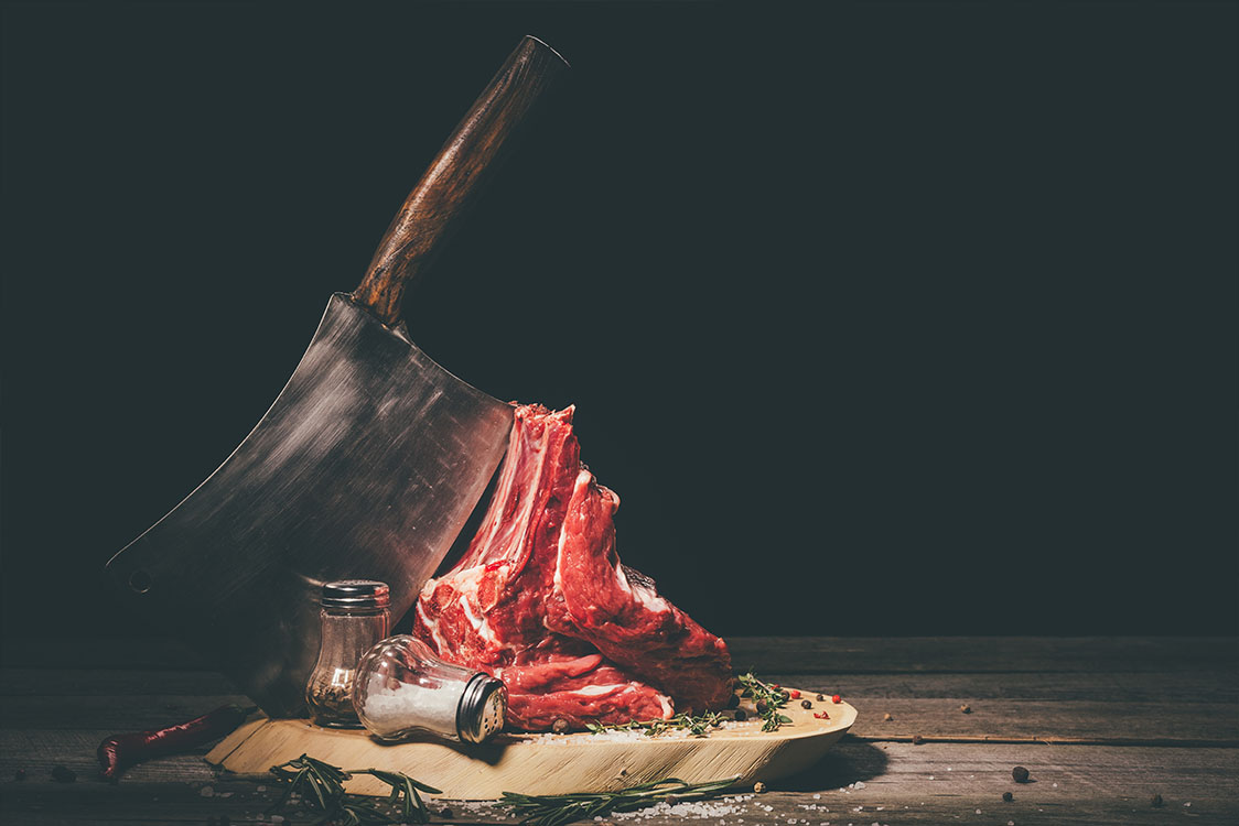 Ruwe varkensribbetjes met slager cleaver