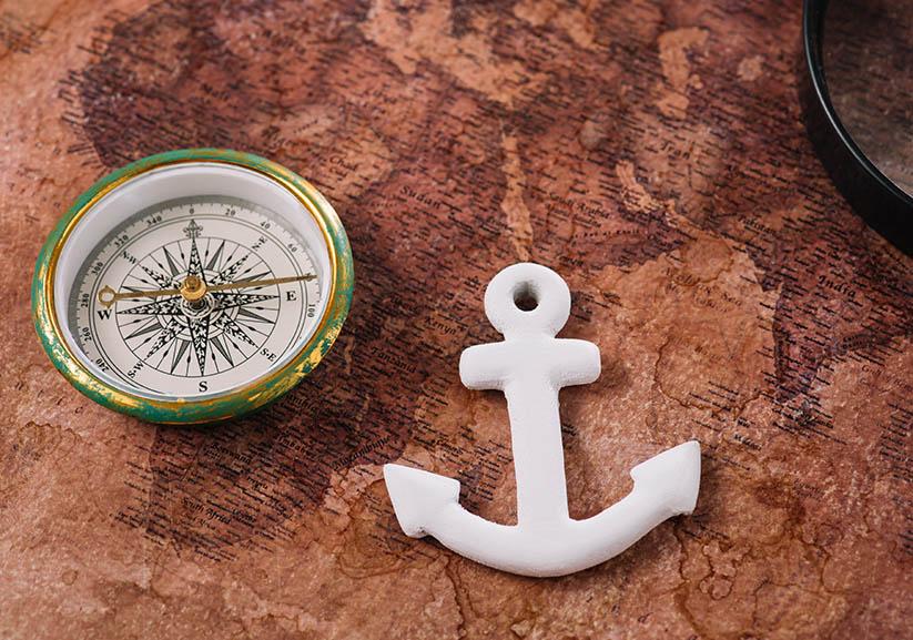 Wit anker nabij kompas op kaart